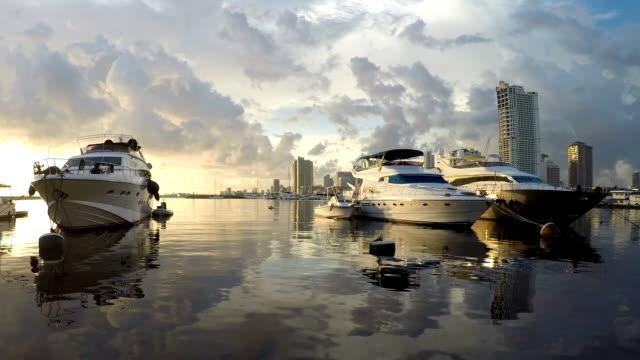 vídeos y material grabado en eventos de stock de yate anclado en la bahía de costa de mar bajo crepúsculo atardecer anochecer. siluetas - yacht