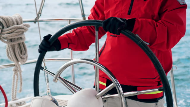 yacht is being controlled by a specialist in a red parka - ster fragment pojazdu filmów i materiałów b-roll