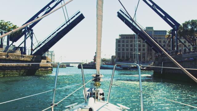 Yacht moving towards harbor under drawbridge