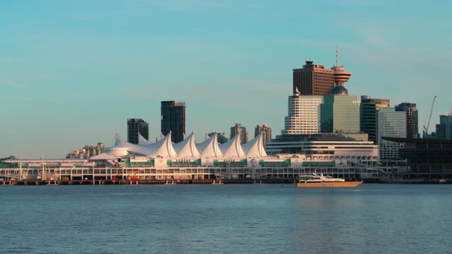Yacht passing in front of Vancouver Downtown. The remote view from Stanley Park across Vancouver Harbor. Accelerated