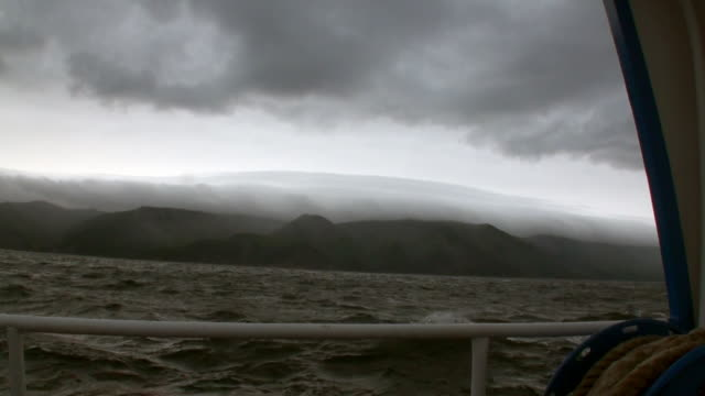 Yacht rails on background of dark gray clouds in sky and storm on Lake Baikal.