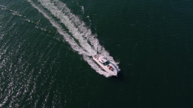 Yacht sailing in sea with young people on deck View from drone of young people on a yacht deck. Group of friends on a yacht deck having party. yacht stock videos & royalty-free footage