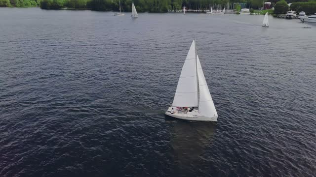Yacht sailing on lake. Sailing boat. Yacht from drone. Yachting video. Yacht from above. Sailboat from drone. Sailing video. Yachting at windy day. Rich and famous lifestyle