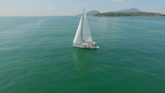 Yacht sailing on open sea at sunny day. Yachting. Yacht video. Yacht drone video. Sailing aerial video. Sailing yacht video