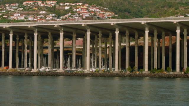 Yacht stop among columns under flight strip of Madeira airport video