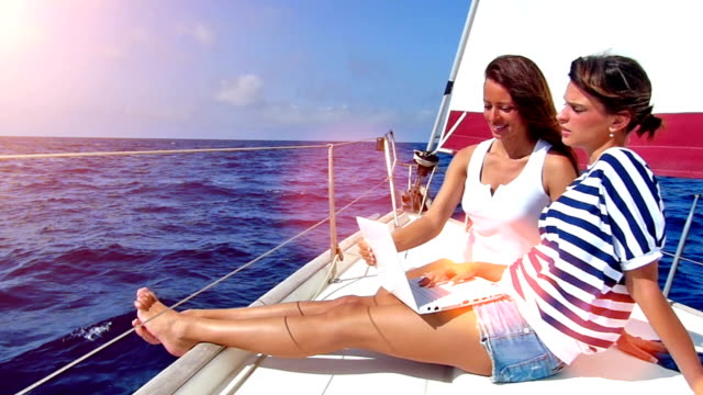 Yacht week! Happy women on the bow of a Sailboat using a laptop,flare light.High speed camera, slow motion yachting stock videos & royalty-free footage