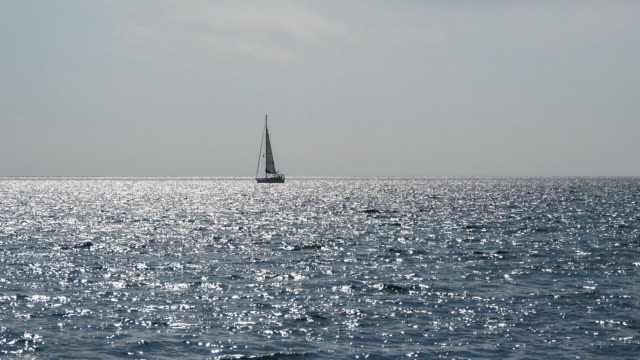 Yacht with sails in calm blue water of sea. Sailboat on horizon in the beautiful landscape. Sailing boat. Yacht sailing on opened ocean. Yachting at windy day. video