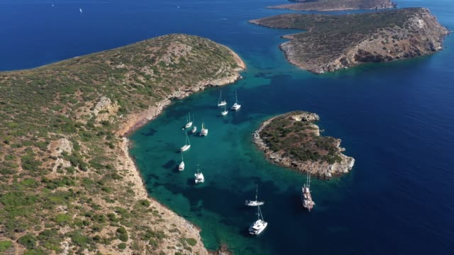 Yachts anchored in a strait near the islands of High quality air video on a summer day. aegean sea stock videos & royalty-free footage