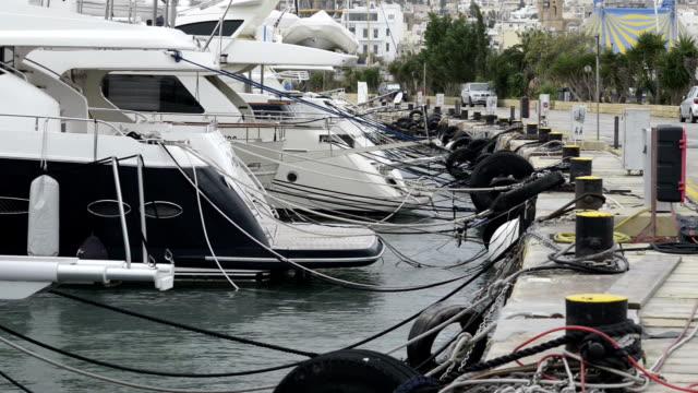 båtar förtöjda vid manoel island marina i malta. segla båtar i rad på lastkajer vid seaside harbor. - skrov bildbanksvideor och videomaterial från bakom kulisserna