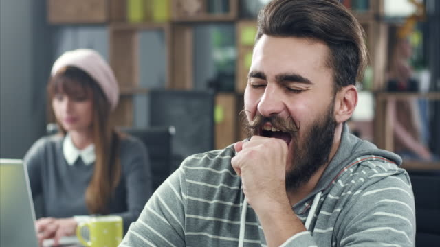 Yawning at workplace Young man yawning at workplace yawning stock videos & royalty-free footage