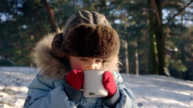 vídeos de stock, filmes e b-roll de 5 ano menino beber chá na floresta de inverno - chocolate quente
