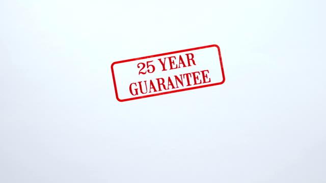 25 jahresgarantie-siegel gestempelt auf blankopapier hintergrund, produktqualität - zahl 25 stock-videos und b-roll-filmmaterial