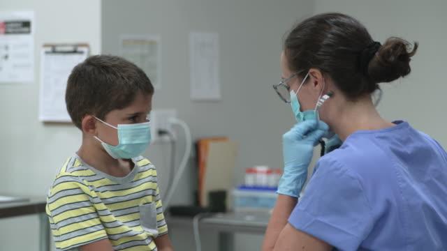 vidéos et rushes de garçon de 6 ans au rendez-vous de médecins utilisant un masque protecteur de visage - enfant masque