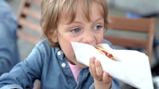 vídeos de stock, filmes e b-roll de menino de 5 anos na camisa jeans, comendo cachorro-quente delicioso. - salsicha