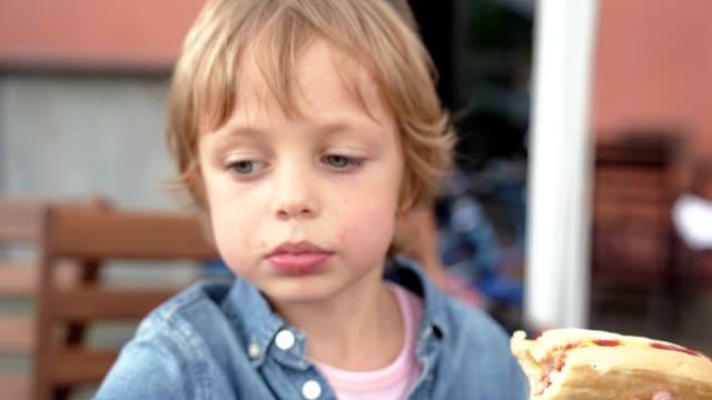 vídeos de stock, filmes e b-roll de menino de 5 anos na camisa jeans, comendo cachorro-quente delicioso. - cachorro quente