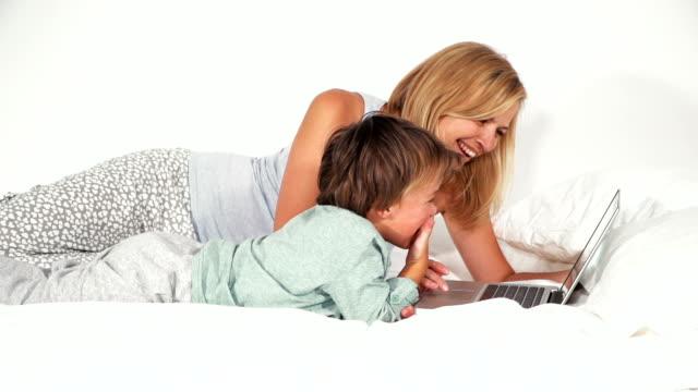 4 jähriger bub liegt mit seiner mutter im bett und spielt mit notebook video