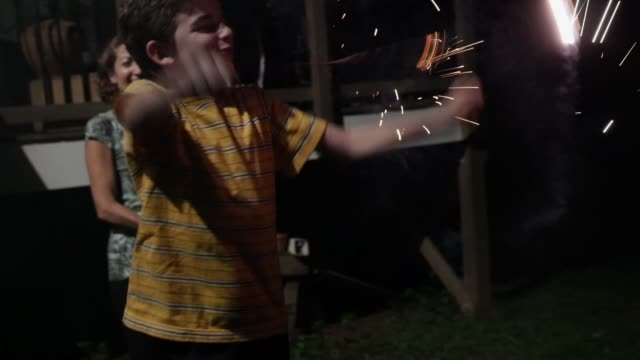 10 -11 year old boy playing with fireworks and sparklers with family in yard Young 10 - 11 year old boy dancing and playing with fireworks and sparklers with his family outside in their yard at night celebrating 4th of July in slow motion family 4th of july stock videos & royalty-free footage