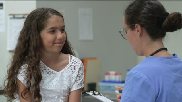 stockvideo's en b-roll-footage met 12 jaar oud meisje bij artsenbenoeming - lagere schoolleeftijd