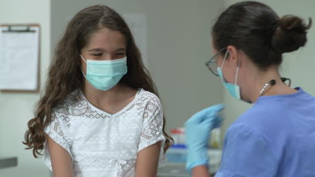 vidéos et rushes de fille de 12 ans au rendez-vous de médecins portant un masque protecteur de visage - enfant masque