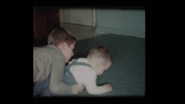 8 year old Little boy plays lovingly with baby brother 1960 video