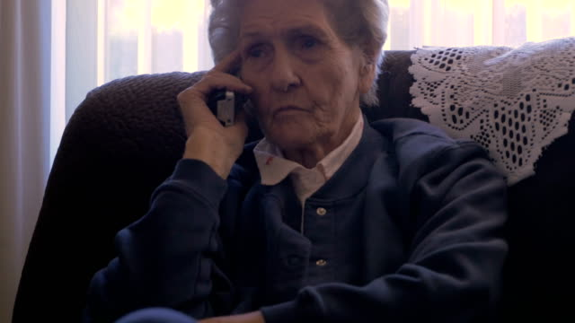 A 90 year old woman on a phone at her home while rubbing her eye in 4k A 90 year old woman listening and talking on a land line, cordless, phone at her home while rubbing her eye dolly shot cordless phone stock videos & royalty-free footage