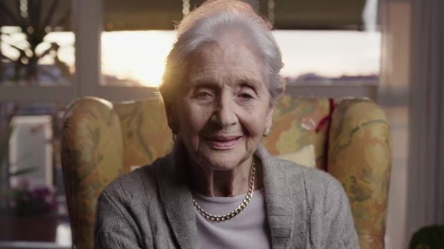 94 anni bella donna anziana ritratto guardando in camera in soggiorno - donne anziane video stock e b–roll
