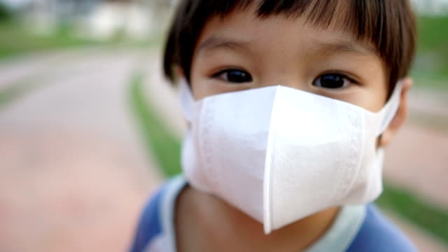 slo mo 3 years old boy wearing pollution masks and looking at camera. - face mask stock videos & royalty-free footage