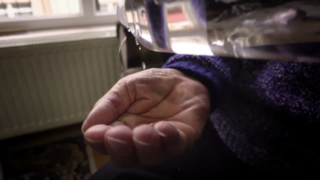 80 years old man cleaning his hands with cologne at his home in slow motion