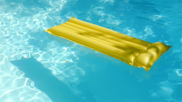 Yellow air mattress floating on blue swimming pool water video