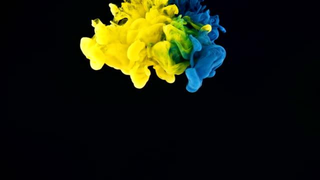 vídeos y material grabado en eventos de stock de salpicaduras de tinta cian y amarillo sobre fondo negro - amarillo color