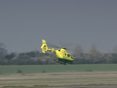 Yellow and green helicopter skims the ground Dramatic helicopter flight. medevac stock videos & royalty-free footage