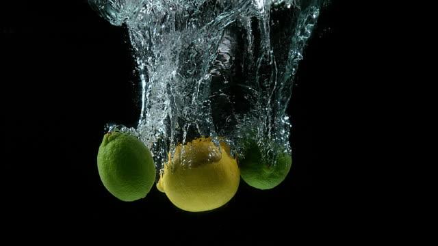 Yellow and green lemons, citrus limonum, Citrus aurantifolia, Fruits falling into Water against Black Background, Slow Motion 4K video