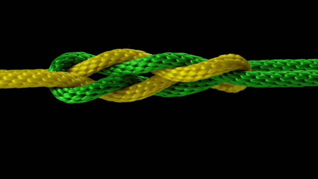 SLO MO LD Yellow and green rope tied into a knot
