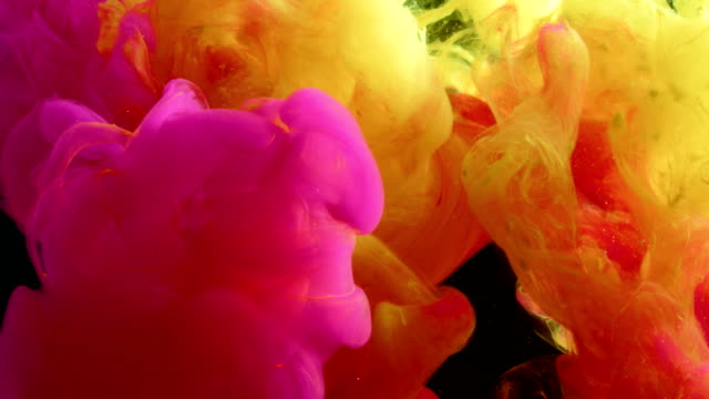 yellow and pink ink mix in a tank of black water. - sfondo multicolore video stock e b–roll