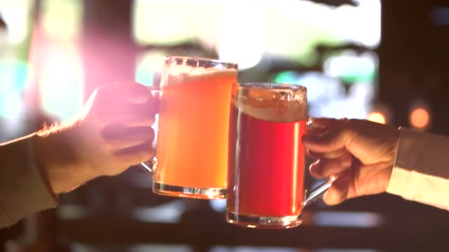 Yellow and red beer clinking, slow-mo. video