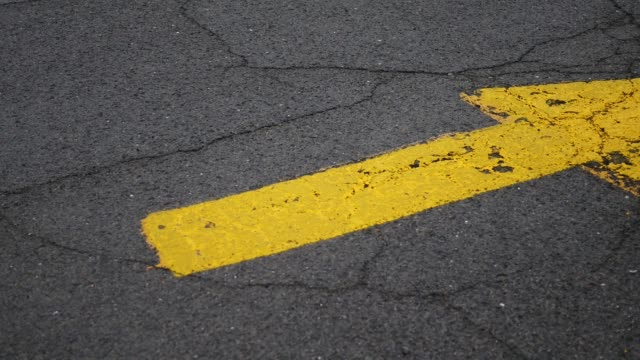 A yellow arrow on the road pointing to a entrance to parking lot video
