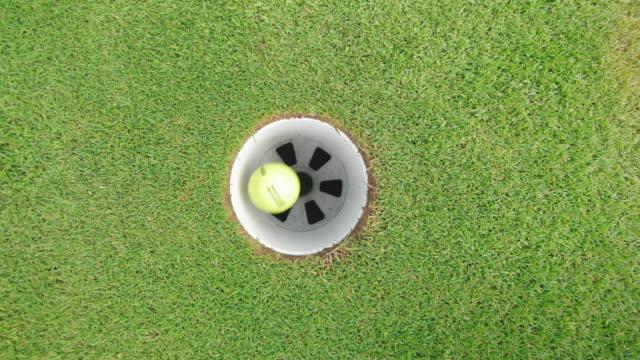 palla gialla che entra in una buca su un campo da golf. - foro video stock e b–roll