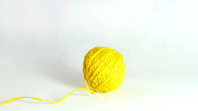 Yellow ball of wool rolls in the middle of the screen. video