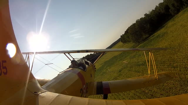 Yellow Biplane Flying Low over Farmland and a House