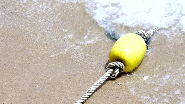 Yellow border float with rope on the beach of sea