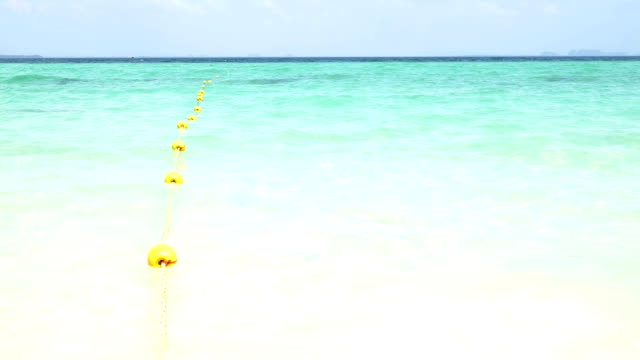 Yellow buoy with wave on the beach