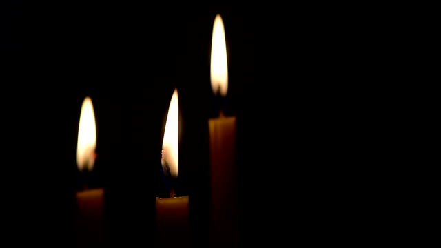 yellow candle lit on black background. video