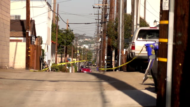 vídeos de stock e filmes b-roll de yellow caution tape swinging on the wind on alley in usa in slow motion 250fps - cercado