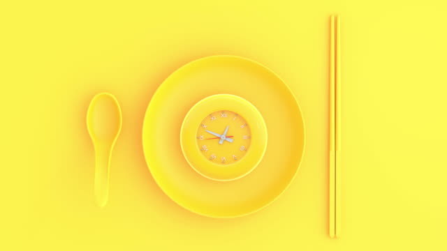 yellow clock in bowl with spoon and chopsticks yellow background - поститься стоковые видео и кадры b-roll