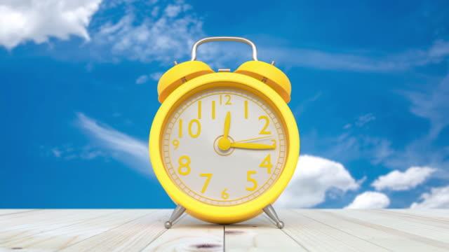 gul klocka på bordet och himmel tid förfaller på den ljusa himlen. - alarm clock bildbanksvideor och videomaterial från bakom kulisserna