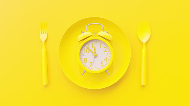 Yellow clock on yellow plate with fork and spoon background