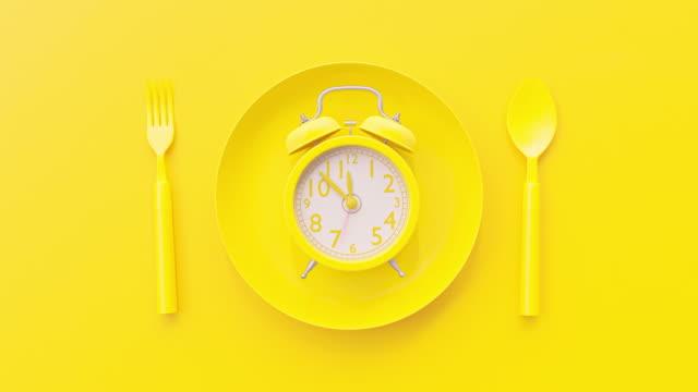 vídeos de stock, filmes e b-roll de relógio amarelo na placa amarela com fundo da fork e da colher - almoço