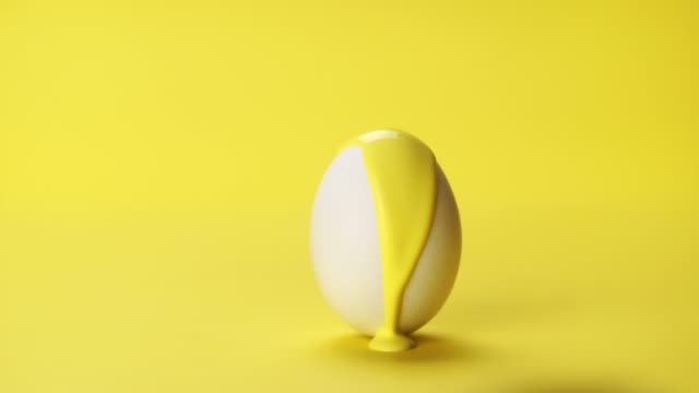 yellow color paint flowing on white egg - tavolozza video stock e b–roll