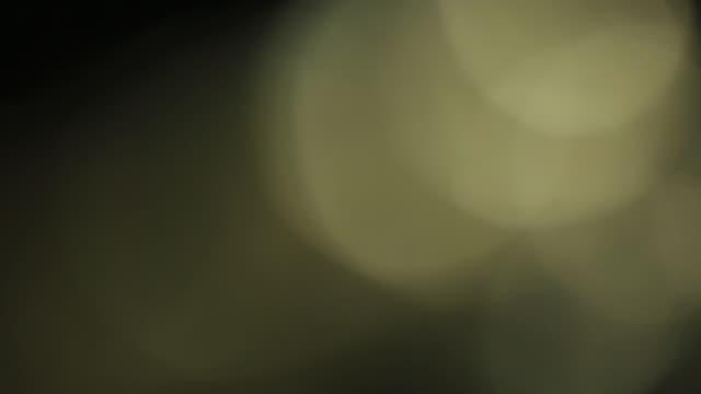gelb gefärbt bokeh impulse und leuchtet. schöne leichte undichtigkeit im warmen farbton auf dunklem hintergrund. echte blendenfleck und leichte undichtigkeit - haartönung stock-videos und b-roll-filmmaterial