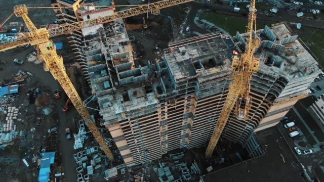 vidéos et rushes de grues de construction jaunes au-dessus des gratte-ciel mouvement aérien - chantier